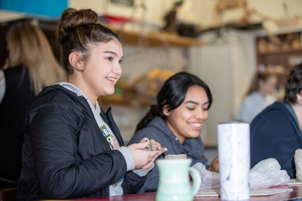 Two students working on their pottery projects.