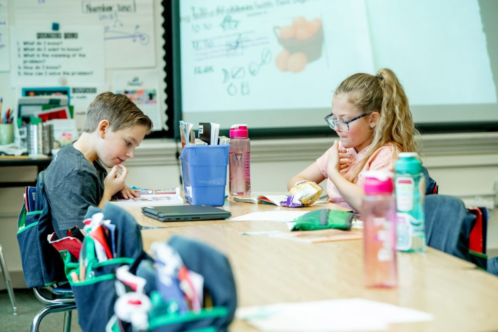 Two students working on an assignment together in their classroom.