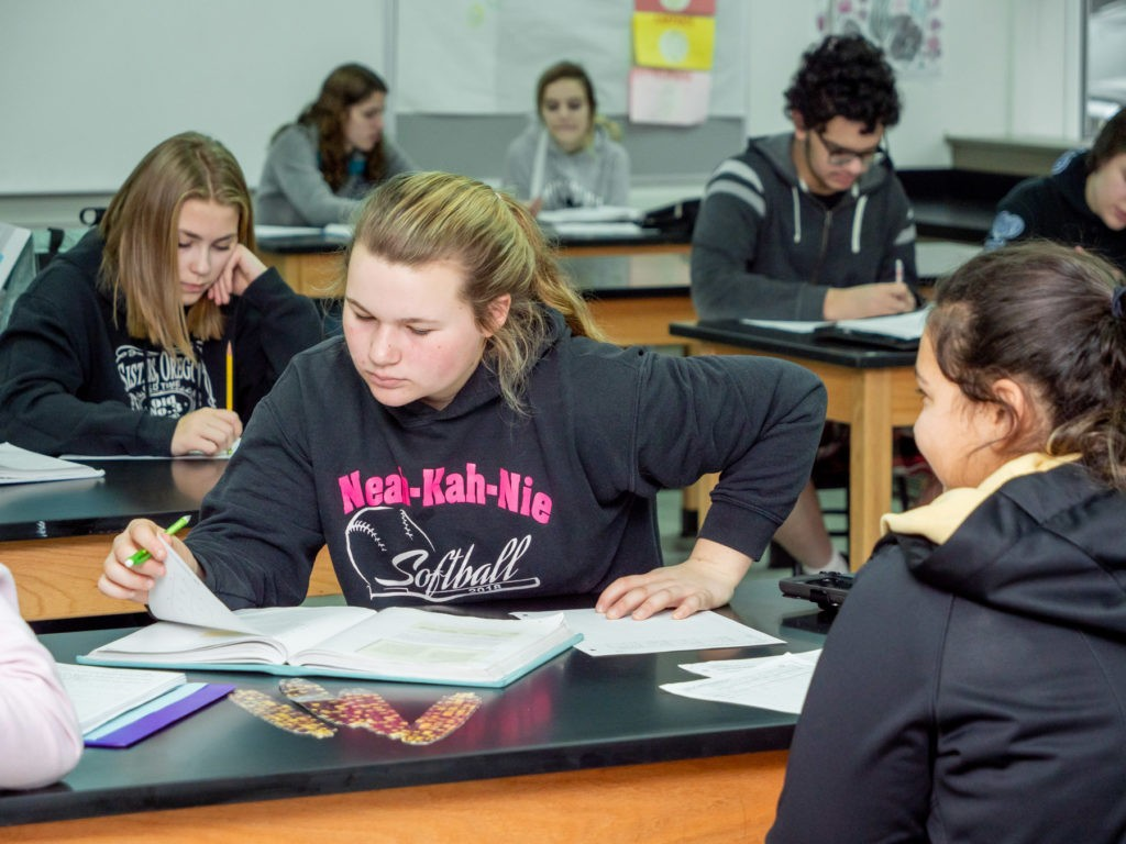 Students reading from textbooks and making notes in class.