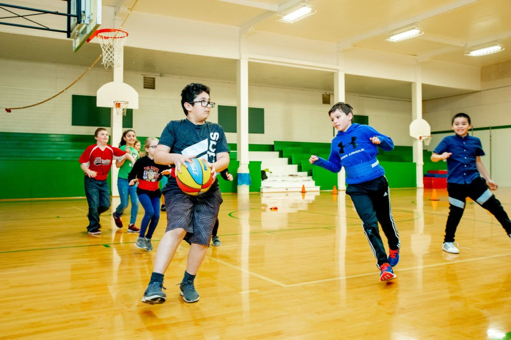 A group of students plays basketball in the school gym.